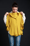 Young brunette woman trying  a shirt on Stock Photos