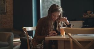 Young brunette woman typing on phone while sitting in restaurant. Beautiful young woman using phone while spending time in cozy restaurant stock video footage