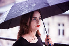 Young brunette woman with umbrella in the rain Royalty Free Stock Photo