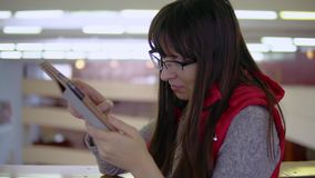 Young brunette woman uses tablet for continuous work in the mall. stock video