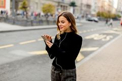 Young brunette woman using mobile while standing on street and Stock Photo
