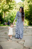 Young brunette woman walking with baby girl at park Stock Images