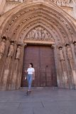A young brunette woman walking in front of the Cathedral of Valencia Spain with white shirt and gray pants royalty free stock photography