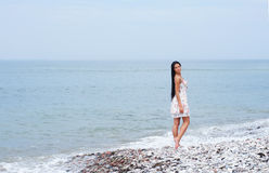 A young brunette woman walking near the sea Royalty Free Stock Image