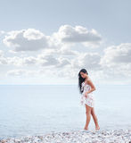 A young brunette woman walking near the sea Stock Images