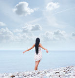 A young brunette woman walking near the sea Royalty Free Stock Photos