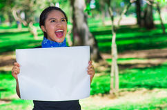 Young brunette woman wearing blue bandana around neck, holding white poster chanting outdoors facing camera, activist Stock Photos