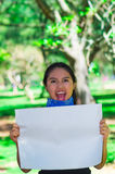 Young brunette woman wearing blue bandana around neck, holding white poster chanting outdoors facing camera, activist Royalty Free Stock Images