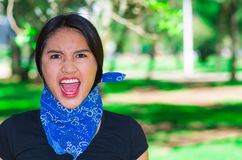 Young brunette woman wearing blue bandana around neck, interacting outdoors for camera, activist protest concept Stock Photography