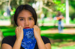 Young brunette woman wearing blue bandana around neck, interacting outdoors for camera, activist protest concept Royalty Free Stock Images
