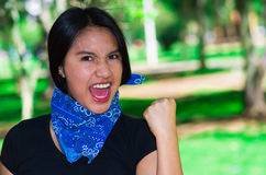 Young brunette woman wearing blue bandana around neck, interacting outdoors for camera, activist protest concept Stock Image