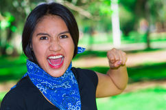 Young brunette woman wearing blue bandana around neck, interacting outdoors for camera, activist protest concept Stock Images