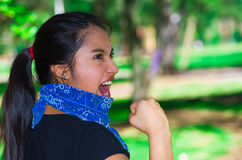 Young brunette woman wearing blue bandana around neck, interacting outdoors for camera, activist protest concept Royalty Free Stock Photos