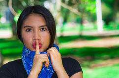 Young brunette woman wearing blue bandana around neck, interacting silence outdoors for camera, activist protest concept Royalty Free Stock Photos