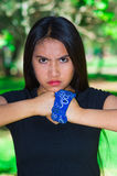 Young brunette woman wearing blue bandana around wrist, interacting angryv for camera outdoors, activist protest concept Stock Photography