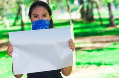 Young brunette woman wearing blue bandana covering half of face, holding white poster outdoors facing camera, activist Royalty Free Stock Images