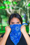 Young brunette woman wearing blue bandana covering half of face, interacting outdoors for camera, activist protest Royalty Free Stock Photo