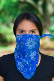 Young brunette woman wearing blue bandana covering half of face, interacting outdoors for camera, activist protest Royalty Free Stock Images