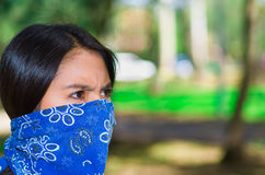 Young brunette woman wearing blue bandana covering half of face, interacting outdoors for camera, activist protest Stock Photo