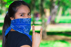 Young brunette woman wearing blue bandana covering half of face, interacting outdoors for camera, activist protest Stock Photography