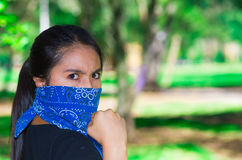 Young brunette woman wearing blue bandana covering half of face, interacting outdoors for camera, activist protest Stock Photos