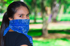Young brunette woman wearing blue bandana covering half of face, interacting outdoors for camera, activist protest Royalty Free Stock Image