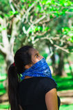Young brunette woman wearing blue bandana covering half of face, interacting outdoors for camera, activist protest Royalty Free Stock Photos