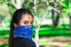 Young brunette woman wearing blue bandana covering half of face, interacting outdoors for camera, activist protest Stock Images