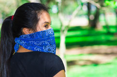 Young brunette woman wearing blue bandana covering half of face, interacting outdoors for camera, activist protest Stock Image