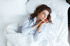 Young brunette woman wearing pajamas in bed at home Royalty Free Stock Image