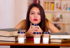 Young brunette woman wearing pink top sitting by desk holding mug looking tired, coffee cups placed on table, student Royalty Free Stock Images