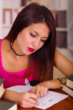 Young brunette woman wearing pink top sitting by desk looking tired, writing on paper during exam using pen, student Stock Photo