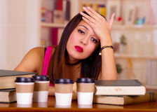 Young brunette woman wearing pink top sitting by desk with stack of books placed on it, resting head onto hand, tired Royalty Free Stock Photos