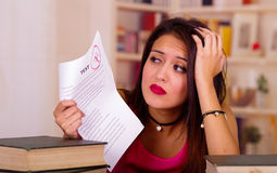 Young brunette woman wearing pink top sitting by desk with stack of books placed on it, resting head onto hand, tired Stock Photos