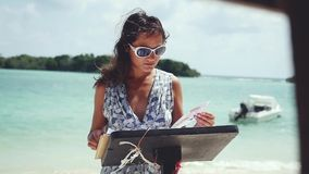 Young brunette woman wearing sunglasses looks at menu in beach restaurant. View of great ocean with boats behind her. Slow motion. 1920x1080. hd stock video
