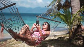 Young brunette woman wearing sunglasses reading sms texting on smartphone lying on hammock relaxing on tropical vacation stock video
