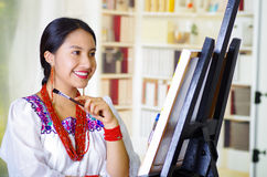 Young brunette woman wearing traditional andean clothing painting on canvas inside studio, evaluating work thoughtful. Bookshelves background Stock Photo