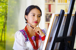 Young brunette woman wearing traditional andean clothing painting on canvas inside studio, evaluating work thoughtful. Garden window background Stock Images
