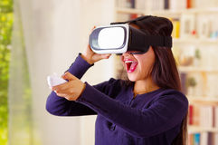 Young brunette woman wearing virtual reality goggles experiencing future technology, interacting and smiling while. Playing, domestic background,vr concept Royalty Free Stock Image