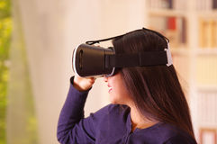 Young brunette woman wearing virtual reality goggles experiencing future technology, interacting and smiling while. Playing, domestic background,vr concept Stock Photo