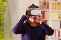 Young brunette woman wearing virtual reality goggles experiencing future technology, interacting and smiling while. Playing, domestic background,vr concept Royalty Free Stock Photo