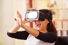 Young brunette woman wearing virtual reality goggles experiencing future technology, interacting and smiling while. Playing, domestic background,vr concept stock image