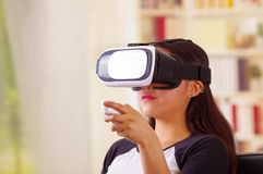 Young brunette woman wearing virtual reality goggles experiencing future technology, interacting and smiling while. Playing, domestic background,vr concept Stock Photography