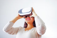 Young brunette woman wearing virtual reality goggles experiencing future technology, interacting and smiling while. Playing, studio background, vr concept Stock Photo