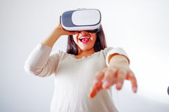 Young brunette woman wearing virtual reality goggles experiencing future technology, interacting and smiling while. Playing, studio background, vr concept Royalty Free Stock Image