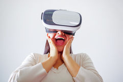 Young brunette woman wearing virtual reality goggles experiencing future technology, interacting and smiling while. Playing, studio background, vr concept Stock Images