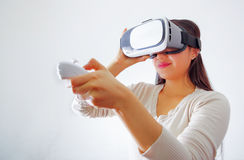 Young brunette woman wearing virtual reality goggles experiencing future technology, interacting and smiling while. Playing, studio background, vr concept Royalty Free Stock Images