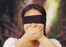 Young brunette woman wearing white sweater, blindfolded with black textile, covering mouth using hands, facing camera. Hostage concept royalty free stock image