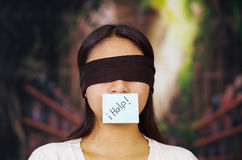 Young brunette woman wearing white sweater, blindfolded with black textile, paper note covering mouth reading help Royalty Free Stock Photos
