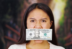 Young brunette woman wearing white sweater covering mouth with twenty dollar bill, facing camera, hostage concept Stock Photo
